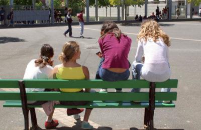 Basse Goulaine, collège de Goulaine, cour de récréation, quatre adolescentes de dos assises sur banc, dont deux assises sur le dossier