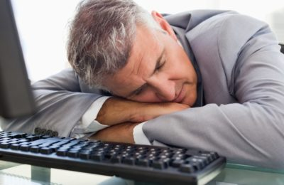 Businessperson sleeping on his desk in his office