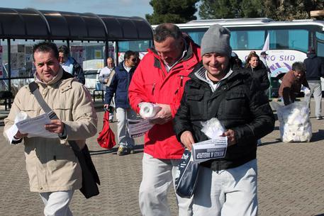 """Migliaia di volantini e rotoli di carta igienica - con etichettati slogan contro il Presidente del Consiglio, Matteo Renzi, e il jobs act - sono stati distribuiti agli operai dello stabilimento di Melfi di Fca da alcuni operai dello stabilimento di Pomigliano d'Arco (Napoli) licenziati nel giugno 2014, da attivisti """"no triv"""" e dei cobas della Campania, Melfi (Potenza), 13 febbraio 2015. La manifestazione, la prima del genere davanti ad una fabbrica di Fca, e' stata organizzata sulla base dell'annuncio di una visita del Presidente del Consiglio a Melfi, la cui data è tuttora da stabilire. ANSA/ TONY VECE"""